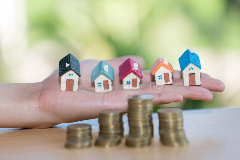 Investor show hand holding a model home and coin , Saving money royalty free stock photo