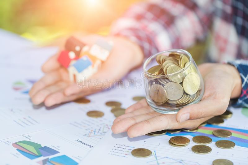 Investor show hand holding a model home and coin , Saving money stock photos