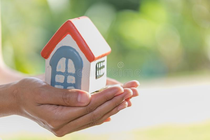 Investor show hand holding a model home and coin , Saving money stock images