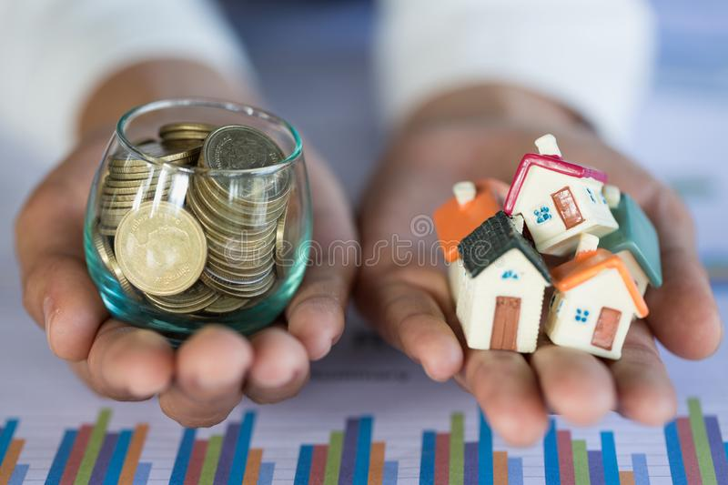 Investor show hand holding a model home and coin , Saving money for buy a new house and loan for plan business investment for real. Estate in the future concept stock photos
