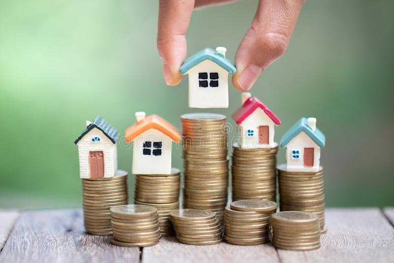 Investor show hand holding a model home and coin , Saving money for buy a new house and loan for plan business investment for real royalty free stock image