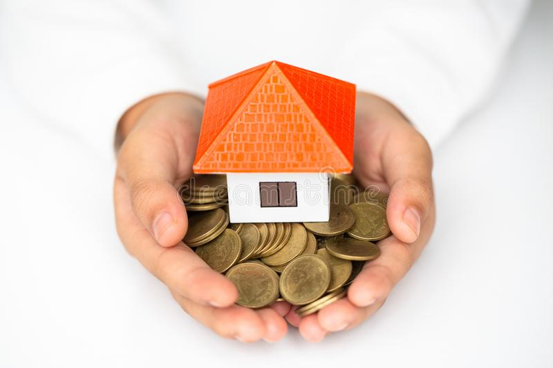 Investor show hand holding a model home and coin on the White Blackground , Saving money for buy a new house and loan for plan stock photo