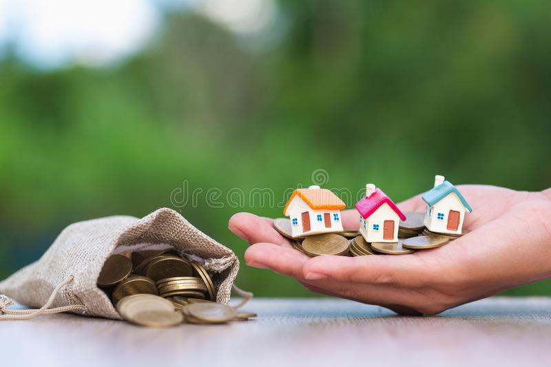 Investor show hand holding a model home , Saving money for buy a new house and loan for plan business investment for real estate. In the future concept royalty free stock image