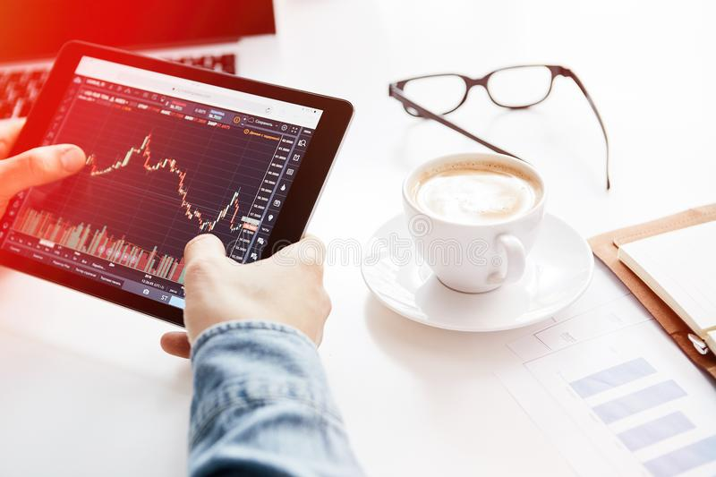 Investor watching the change of stock market on tablet. Cryptocurrency trading platform. Investor watching the change of stock market on tablet. Cryptocurrency stock images