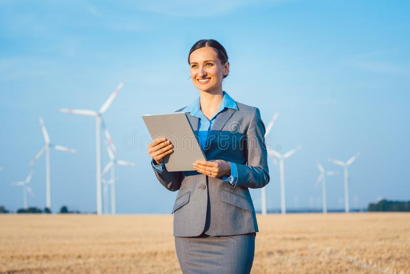Investor in wind turbines with computer evaluating her investment on site. Looking pleased royalty free stock photo
