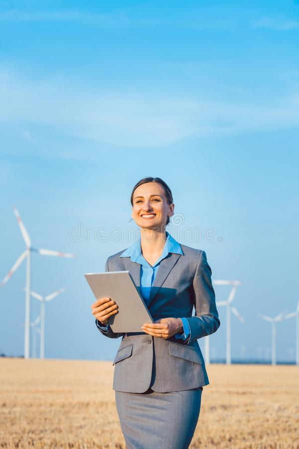 Investor in wind turbines with computer evaluating her investment on site. Looking pleased royalty free stock image