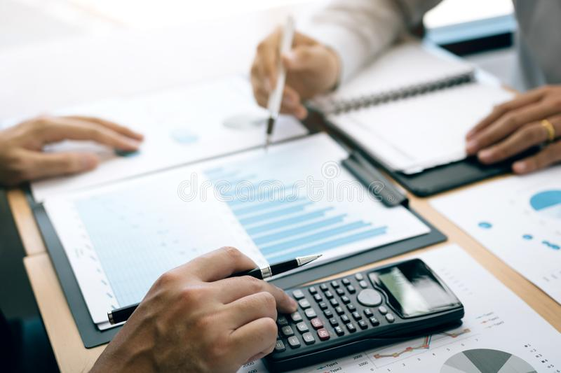 Investors or business people collaborating to analyze the cost graph of the company together at the office royalty free stock image