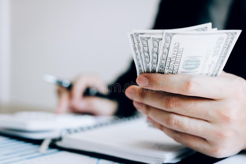 Investors are calculating on calculator investment costs and holding cash notes in hand stock images