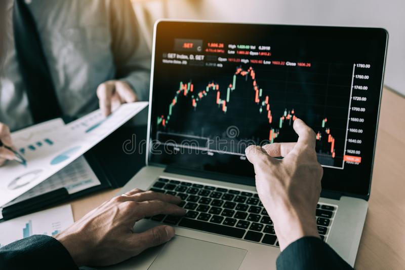 Investors are pointing to laptops that have investment information stock markets and partners taking notes and analyzing stock images