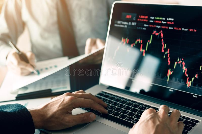 Investors are using laptops entering investment websites stocks market and partners are taking notes and analyzing performance. Data royalty free stock images