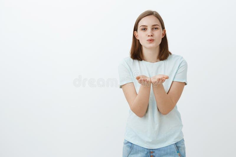Inviando bacio dolce dall'aria Ritratto della donna sveglia spensierata affascinante in maglietta d'avanguardia che piega verso l fotografia stock
