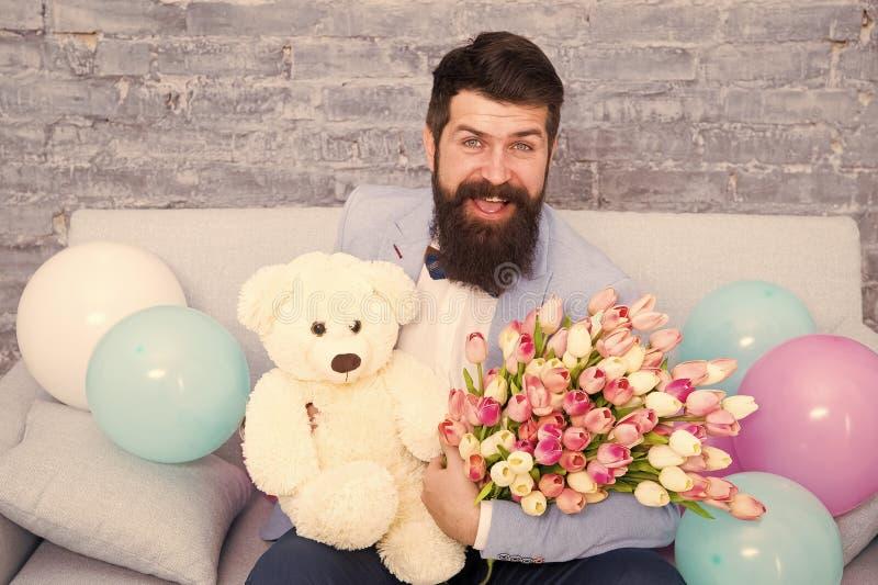 Inviate fiori come se lo dicessi Fiore per 8 marzo Uomo barbuto con tulipano bouquet e orso Appuntamento d'amore internazionale immagini stock