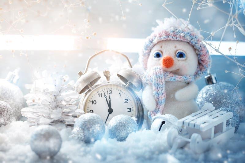 Invierno de la Navidad un fondo, el pequeño muñeco de nieve se coloca con un reloj Feliz Año Nuevo Feliz Navidad fotos de archivo libres de regalías