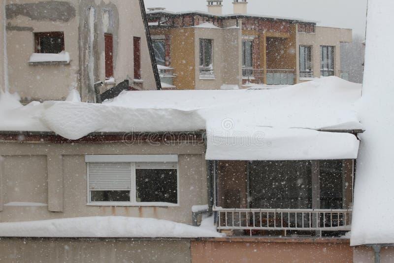 Invierno La nieve peligrosa cae de los tejados de los edificios Invierno con las nevadas pesadas Tejados helados Carámbanos pelig fotografía de archivo libre de regalías