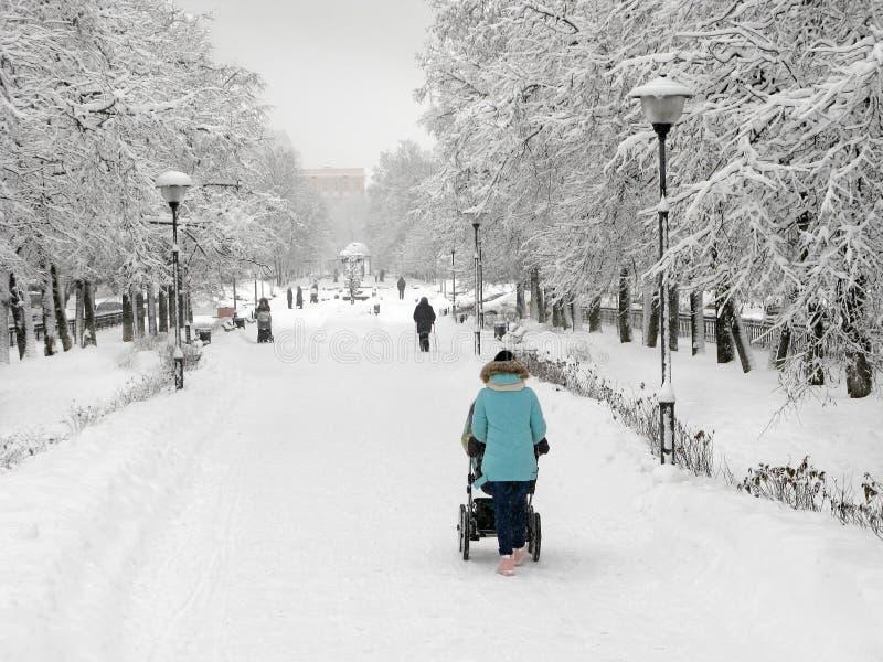 Invierno, madre con el cochecito al aire libre fotos de archivo libres de regalías
