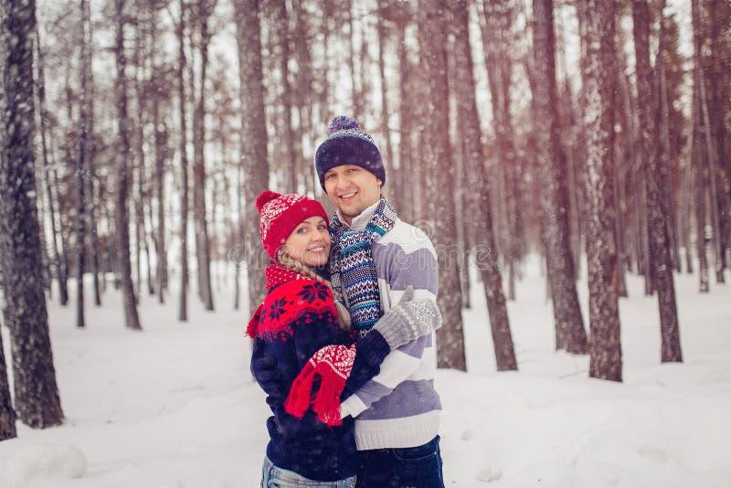 Invierno, moda, concepto de los pares - hombre sonriente y mujer en los sombreros y la bufanda que abrazan sobre fondo del bosque imagen de archivo