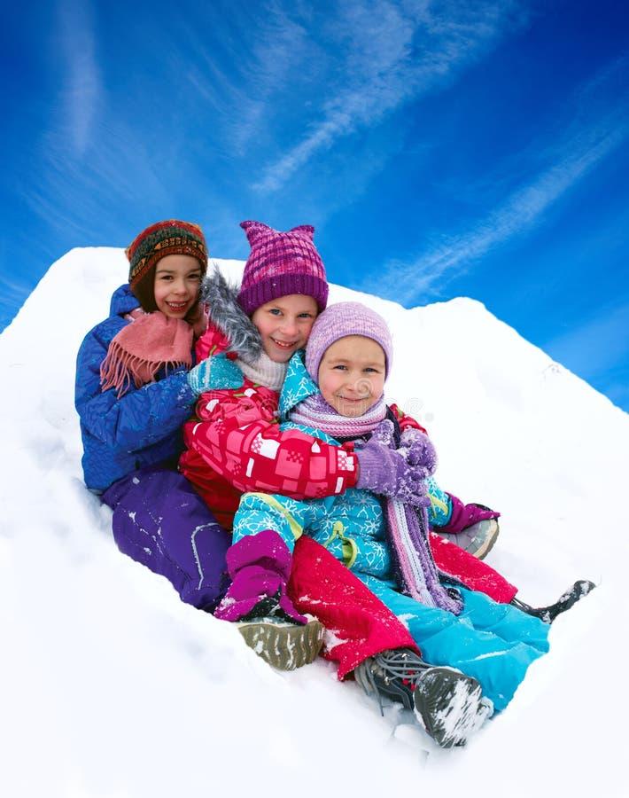 Invierno, niños felices sledding en invierno imagenes de archivo