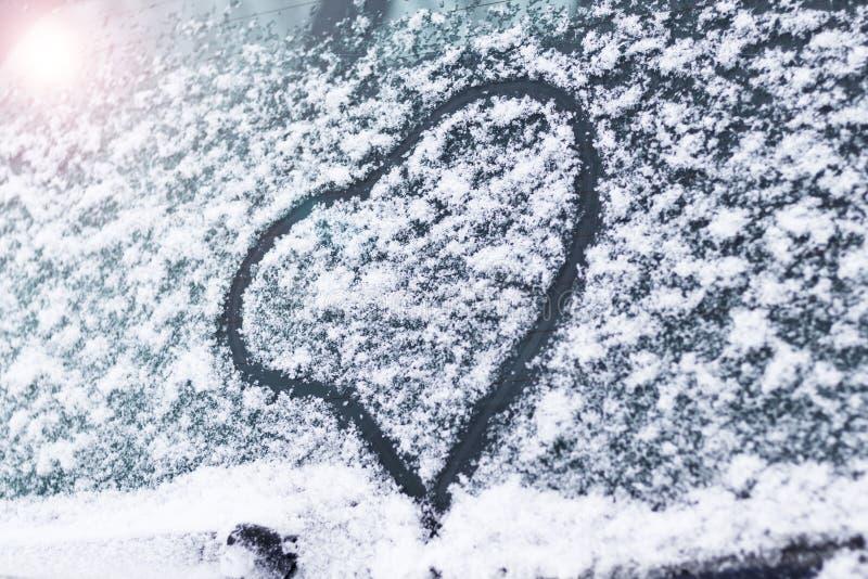 Invierno, nieve, fría en el corazón pintado de cristal del coche está entonando fotos de archivo