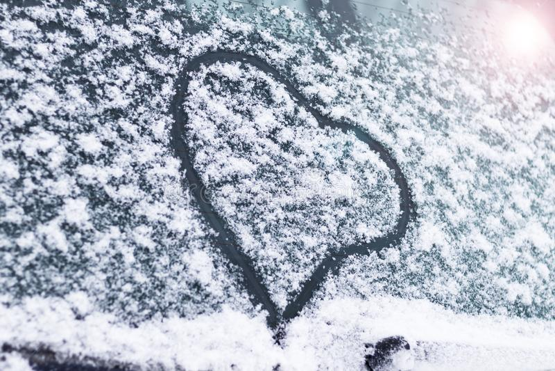 Invierno, nieve, fría en el corazón pintado de cristal del coche está entonando imagen de archivo