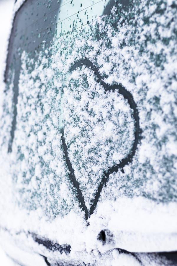 Invierno, nieve, fría en el corazón pintado de cristal del coche está entonando imágenes de archivo libres de regalías