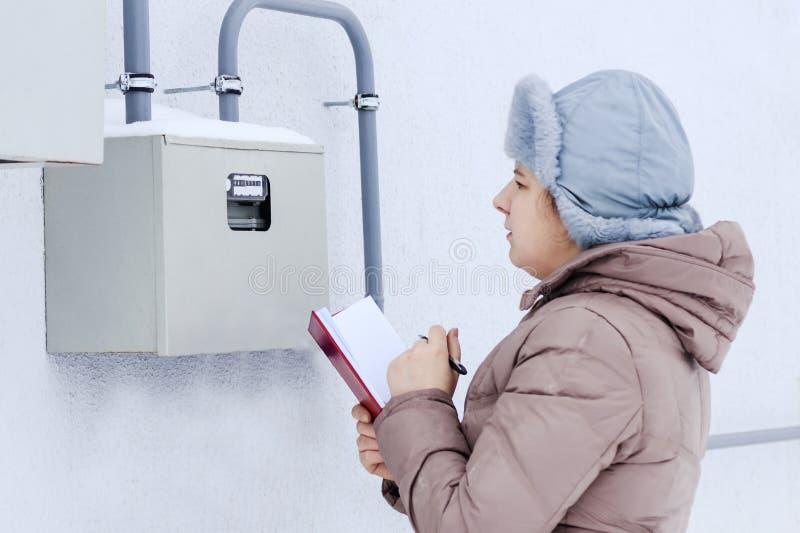 Invierno, nieve, fría la muchacha, el ingeniero, el trabajador registra las lecturas de los sensores y de los indicadores de pres imágenes de archivo libres de regalías