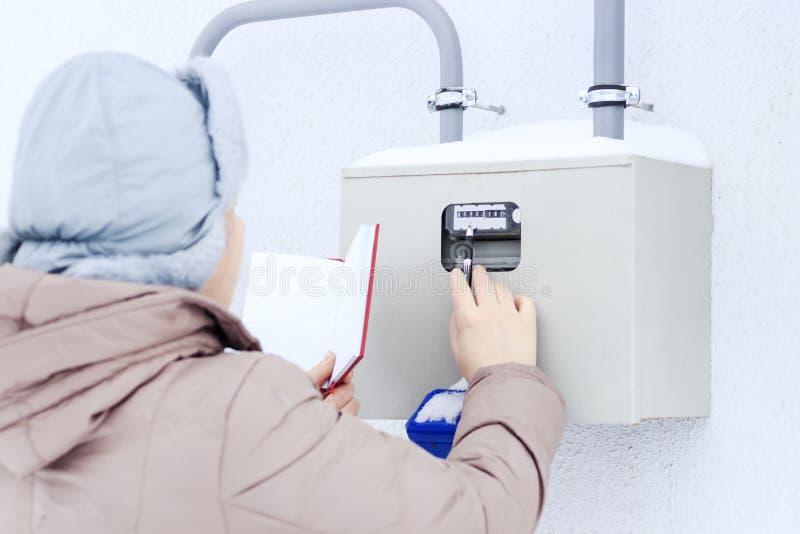 Invierno, nieve, fría la muchacha, el ingeniero, el trabajador registra las lecturas de los sensores y de los indicadores de pres fotografía de archivo