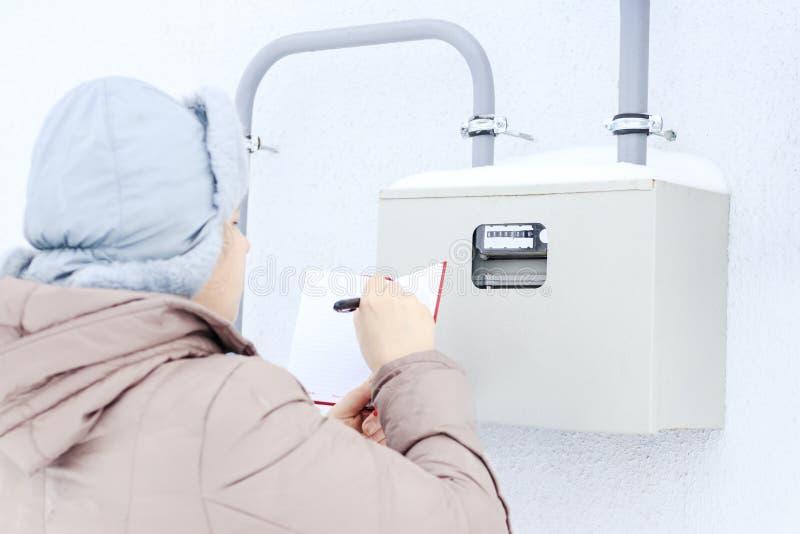 Invierno, nieve, fría la muchacha, el ingeniero, el trabajador registra las lecturas de los sensores y de los indicadores de pres imagen de archivo