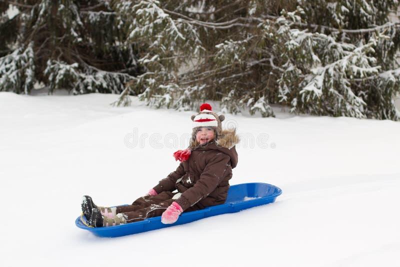 Invierno sledding de la nieve del trineo del trineo largo de la muchacha que se sienta imagen de archivo libre de regalías