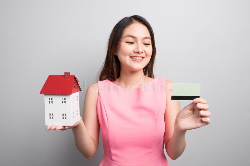 Invierta en concepto de las propiedades inmobiliarias Mujer que sostiene la pequeña casa del juguete y imagenes de archivo