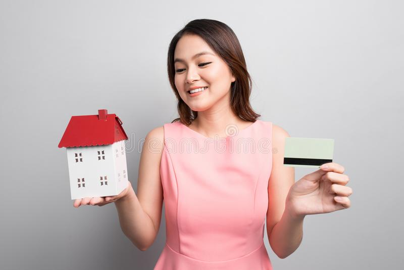 Invierta en concepto de las propiedades inmobiliarias Mujer que sostiene la pequeña casa del juguete y imagen de archivo libre de regalías