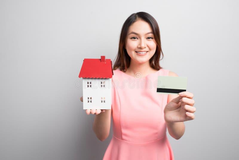Invierta en concepto de las propiedades inmobiliarias Mujer que sostiene la pequeña casa del juguete y fotografía de archivo libre de regalías