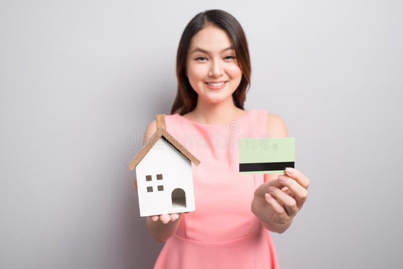 Invierta en concepto de las propiedades inmobiliarias Mujer que sostiene la pequeña casa del juguete y imágenes de archivo libres de regalías