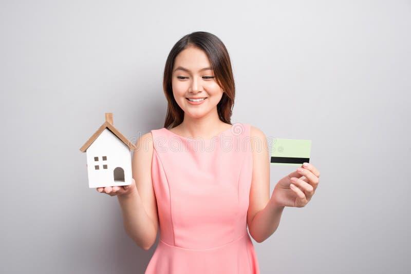 Invierta en concepto de las propiedades inmobiliarias Mujer que sostiene la pequeña casa del juguete y fotos de archivo libres de regalías