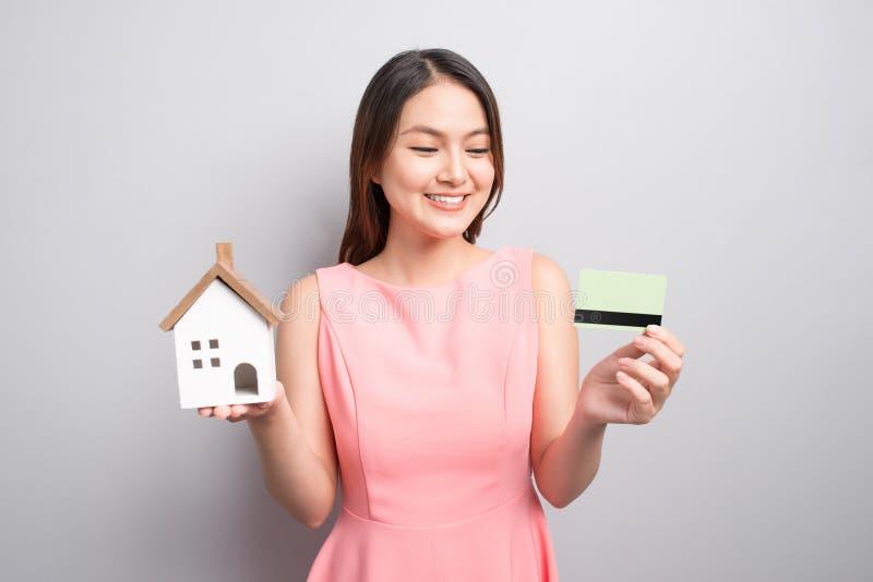 Invierta en concepto de las propiedades inmobiliarias Mujer que sostiene la pequeña casa del juguete y foto de archivo