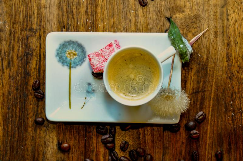 An invigorating cup of coffee surrounded by a painted and lively dandelion. With a delicious dessert on the edge of the plate royalty free stock images