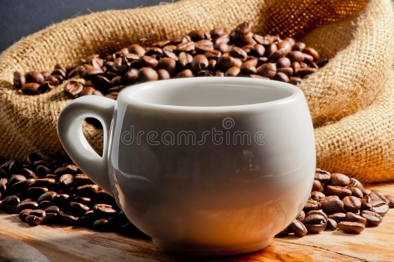 Invigorating drink in a cup and coffee beans. Closeup of invigorating drink in a cup and coffee beans stock image