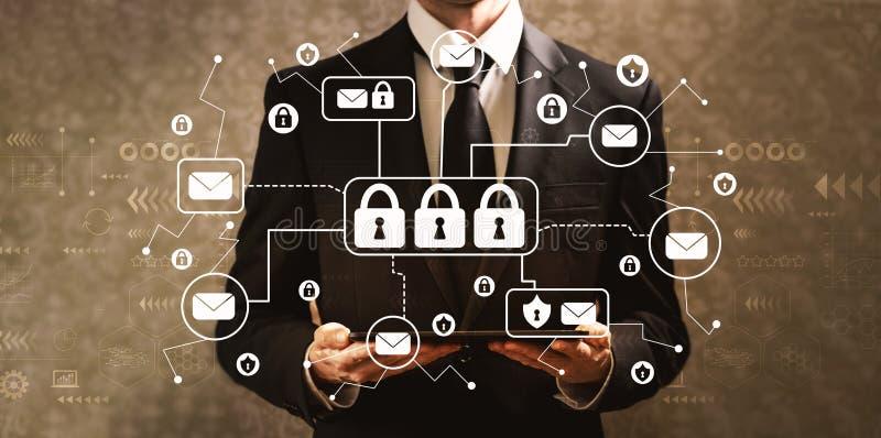 Invii con la posta elettronica il tema di sicurezza con l'uomo d'affari che tiene un computer della compressa fotografia stock libera da diritti