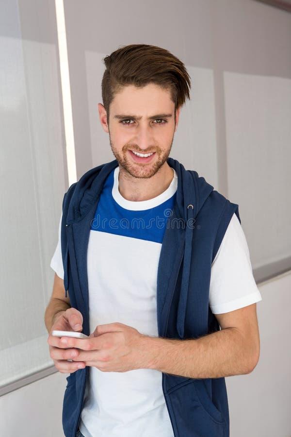 Invio di messaggi di testo bello del giovane immagine stock