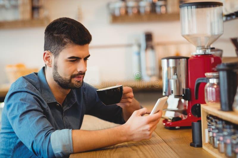 Invio di messaggi di testo del giovane sul telefono cellulare mentre mangiando caffè fotografia stock libera da diritti