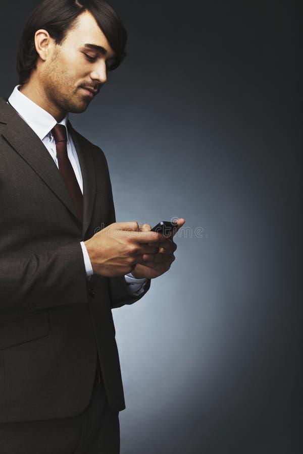 Invio di messaggi di testo dell'uomo d'affari su un telefono cellulare fotografia stock libera da diritti