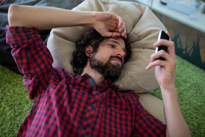 Invio di messaggi di testo dell'uomo sul telefono mobile fotografia stock libera da diritti