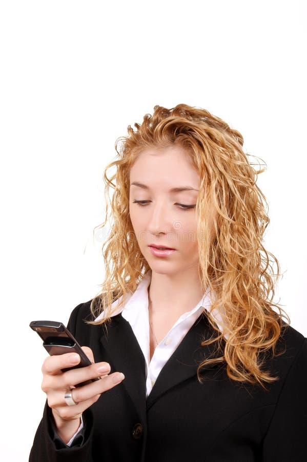 Invio di messaggi di testo della donna di affari sul mobile fotografie stock