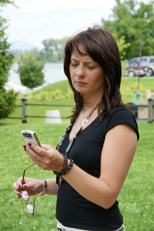 Invio di messaggi di testo della donna di affari sul telefono cellulare fotografia stock libera da diritti