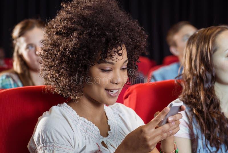 Invio di messaggi di testo della donna sul suo cellulare durante il film fotografia stock libera da diritti