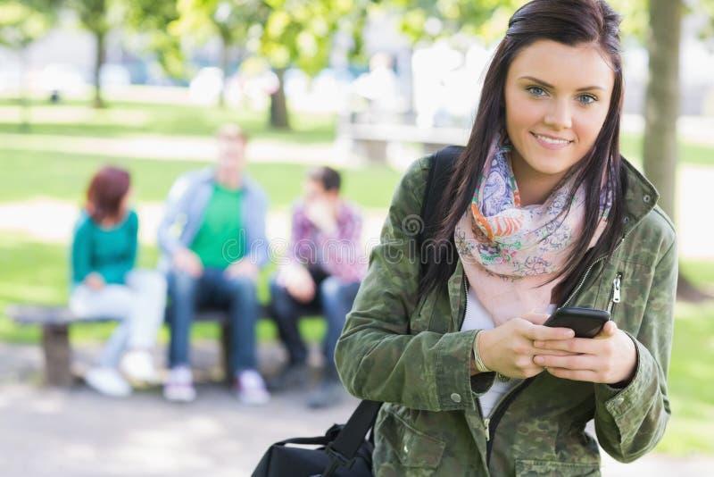 Invio di messaggi di testo della studentessa di college con gli studenti vaghi in parco immagini stock libere da diritti