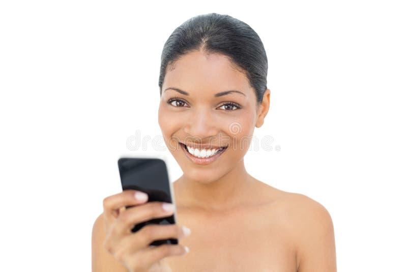 Invio di messaggi di testo di modello moro allegro fotografia stock