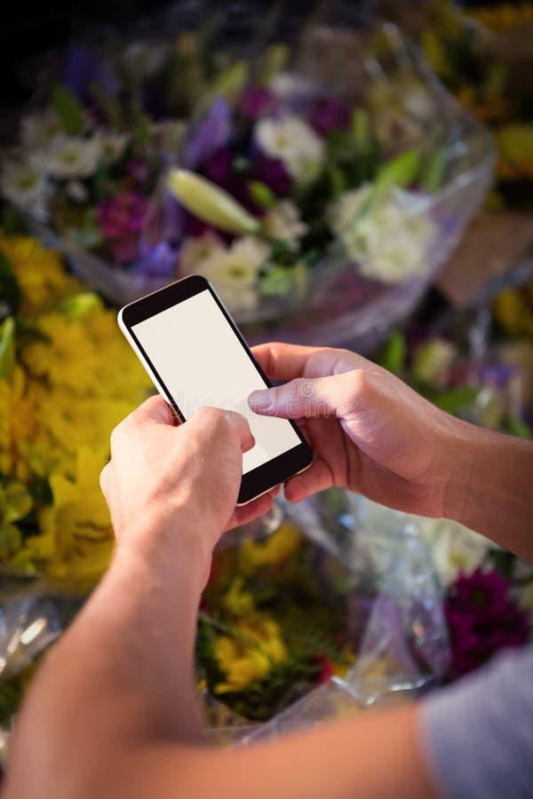 Invio di messaggi di testo maschio del fiorista sul telefono cellulare fotografie stock libere da diritti