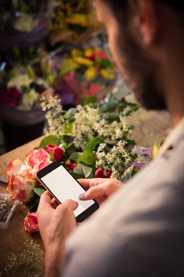 Invio di messaggi di testo maschio del fiorista sul telefono cellulare immagine stock