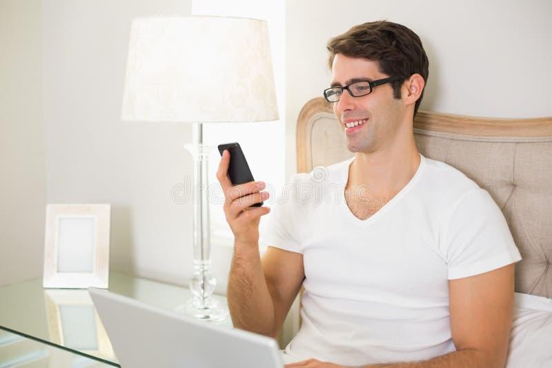 Invio di messaggi di testo sorridente casuale dell'uomo a letto immagine stock