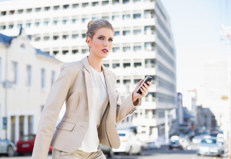 Invio di messaggi di testo splendido aggrottante le sopracciglia della donna di affari immagini stock libere da diritti